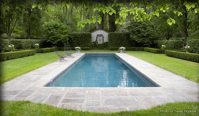 A white-and-green formal garden frames a dramatic pool area. Rosborough Partners