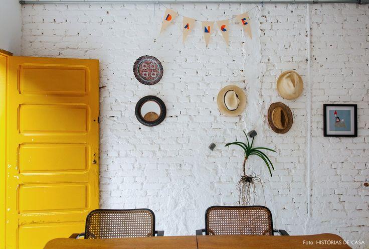 Cozinha com porta amarela e parede galeria de tijolinho branco.