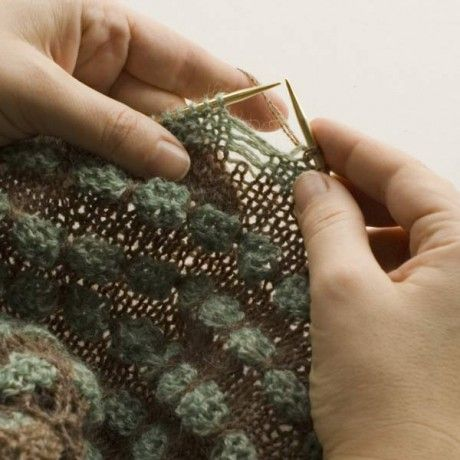 "This explains the method of knitting for ""pop spots""--  they are not bobbles. Instead, this involves dropping stitches and then bundling several laddered threads together.  Clever!"