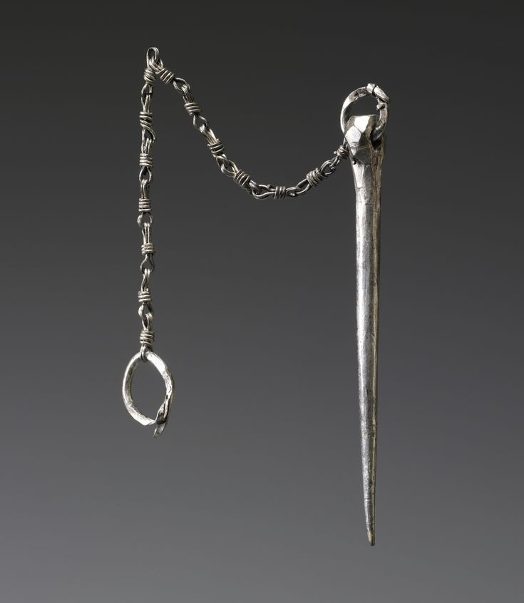 Viking 10th century silver pin with polyhedral-shaped head, slip-knot ring, and attached chain that is a unique find from Ireland. Another pin was originally attached to the now empty ring on the other end of the chain to form a pair of pins. Paired and chain-linked pins were made in Scandinavia and have been found in Swedish Viking burials. This pin came from an Irish crannog (lake-dwelling) of a regional Irish king. It was imported to Ireland through trade, marriage, or raiding.