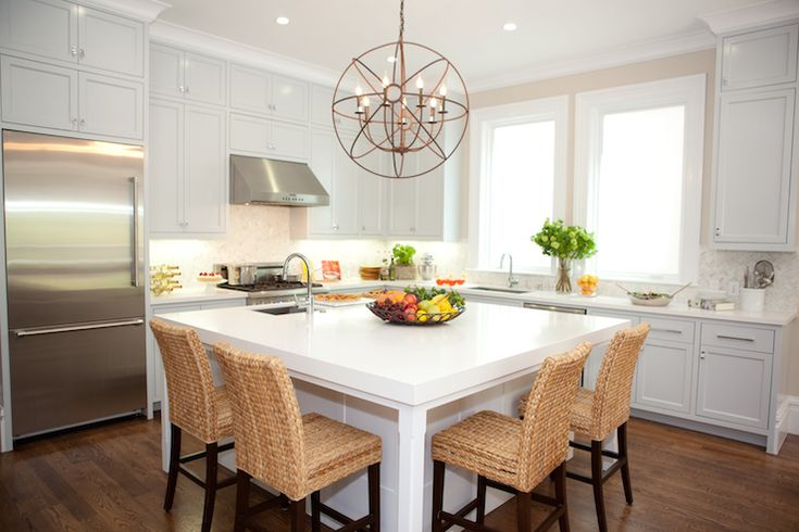 Beautiful L-shaped kitchen with square kitchen island featuring a stainless steel prep sink with gooseneck faucet framed by white quartz counter lined with seagrass counter stools illuminated by a Restoration Hardware Foucault's Iron Orb Chandelier.