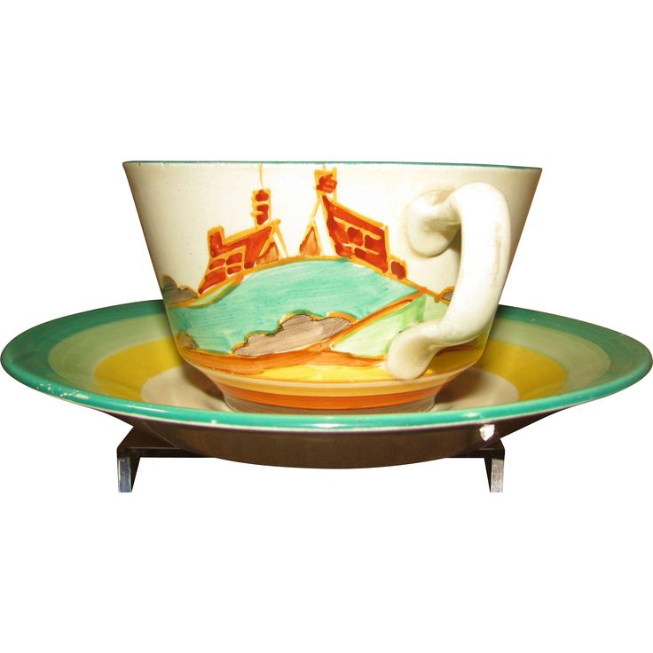An Athens-shaped cup and saucer made in England in Clarice Cliff's workshop circa 1935, hand-painted with the Secrets design.  It has the roofs and