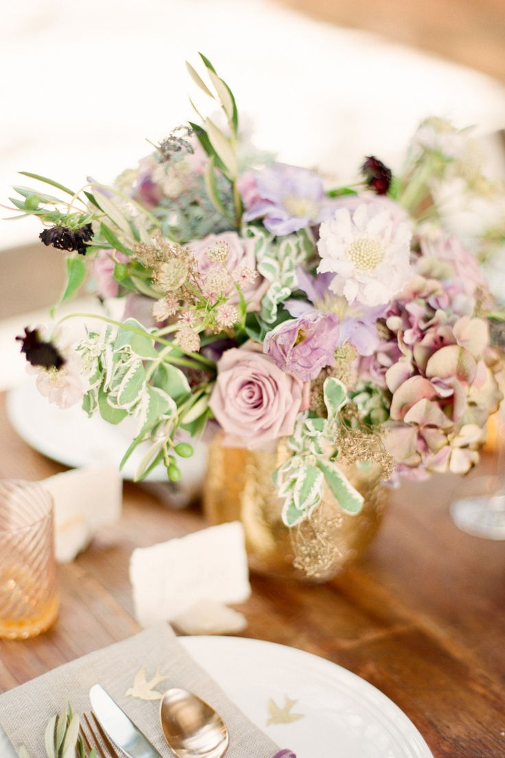 Soft lavender centerpiece in a sparkly gold vase includes roses, hydrangea, scabiosa flowers, lisianthus, chocolate cosmos, clematis, snow on the mountain and olive branches.