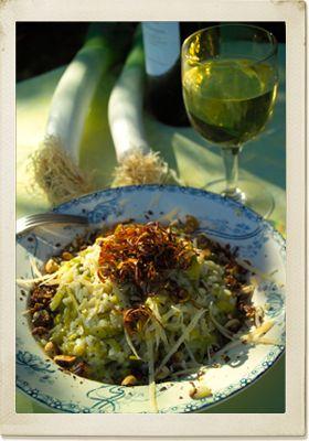 Ingrediënten: Voor 4 personen: 750 g middelgrote prei zonnebloemolie zout 4 sjalotjes, fijngesneden 4 el boter 400 g risottorijst (arborio) 2 glazen niet te droge witte wijn nootmuskaat 1,5 l bouillon van 2 blokjes 100 g oude kaas, geraspt 1 el hazelnootolie of goede olijfolie 150 g hazelnoten, gepeld, droog geroosterd en gehakt oude kaas, grof geraspt zwarte peper, fijngemalen