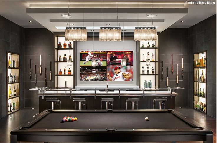 Modern man cave with an illuminating bar, a black pool table, open shelving all around and of course, four TVs in front. Who wants it?