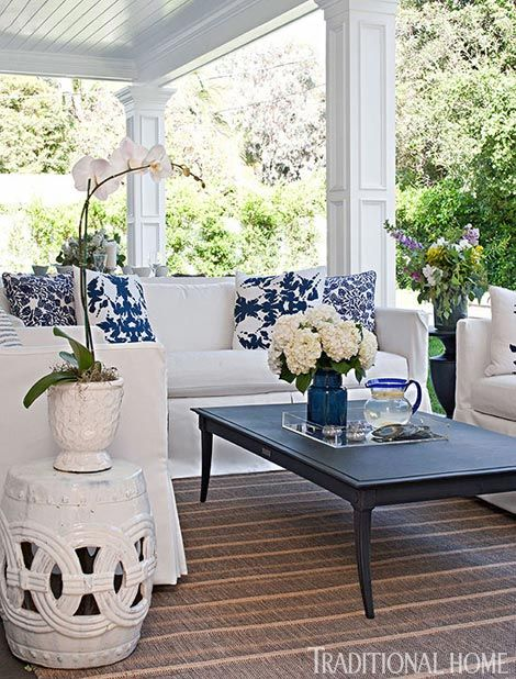 Bill and Giuliana Rancic's covered porch features a classic blue-and-white palette and simple patterns - Traditional Home® / Photo: Michael Garland / Design: Lonni Paul