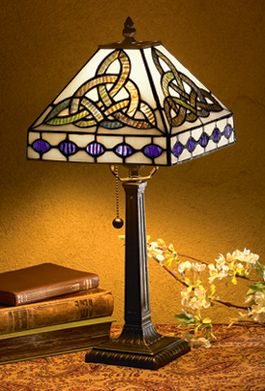 """Trinity Knot Lamp:  Reminiscent of highly prized Tiffany lamps of the late 19th century, this is a classic with a Celtic twist. Leaded glass knots in vivid shades of blue and deep violet glow against a background of luminous ivory-tone glass, all atop a decorative bronze-finished metal base. Ideal size for foyer, desk or bedside, lamp measures 18"""" in height."""
