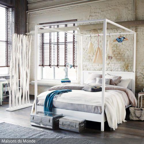 Das weiße Himmelbett vor der Mauerwand verleiht dem Raum einen natürlichen Charme. Mit schlichter Dekoration und minimalistischer Einrichtung mit natürlichen…