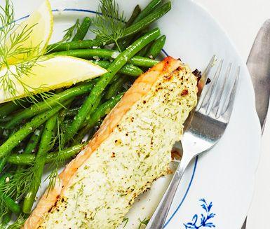 Den här trevliga laxrätten får en kräm av crème fraiche, dijonsenap och dill på toppen innan den sätts in i ugnen. Den dillbakade fisken serveras med pressad potatis, haricots verts och citron.