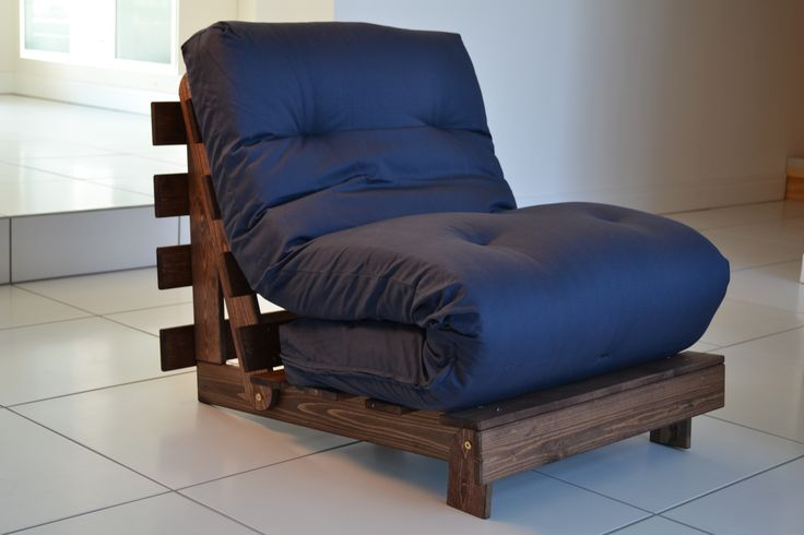 A blue futon folded up onto a brown DIY wood pallet chair.