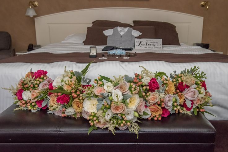 Wedding Photographer - Candid Photos of a Lifetime  Beautiful bouquets, oranges, pinks, whites, creams, green, buds, with pageboy suit in the background