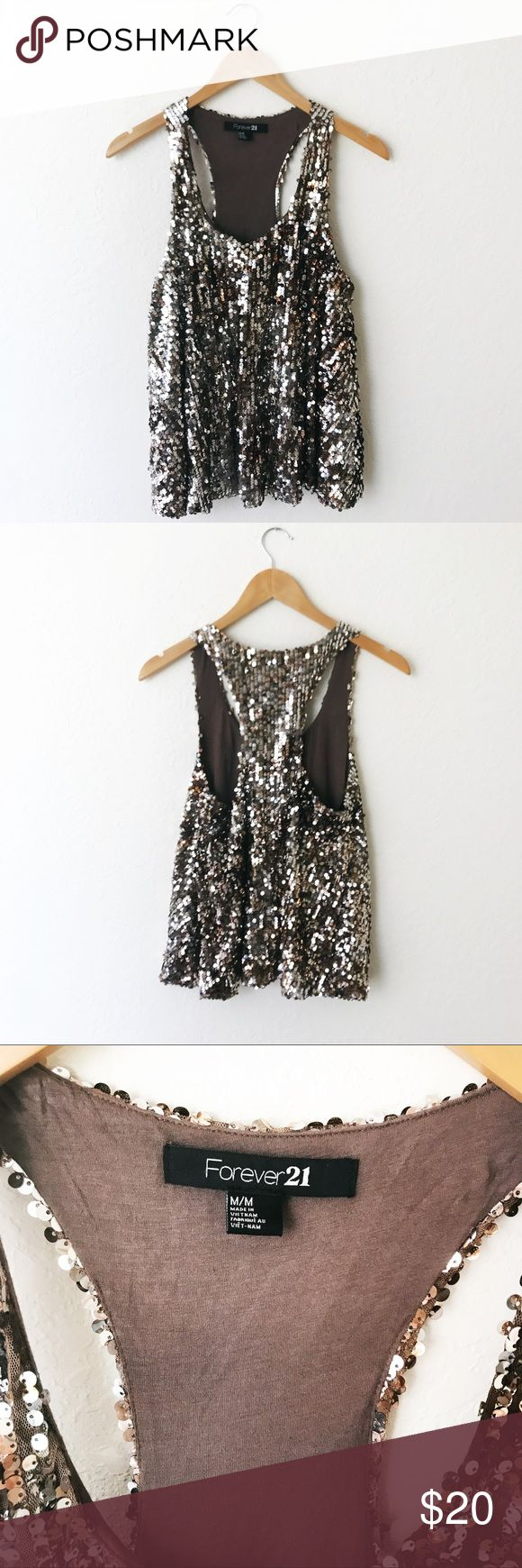 """Sparkly Bedazzled Sequin Racerback Tank Top Excellent preowned condition. Worn once for a New Year's party. Fun and festive Tank totally embellished throughout with a sort of silver/gold sequin design on a brown background. Bottom part is flowy and is not fitted. Such a fun and festive top! Great for the holidays. Approximate measurements when laid flat: 18"""" bust, 24"""" length. Has stretch, inside is lined with soft fabric so it's not itchy and is comfy to wear. Forever 21 Tops Tank Tops"""