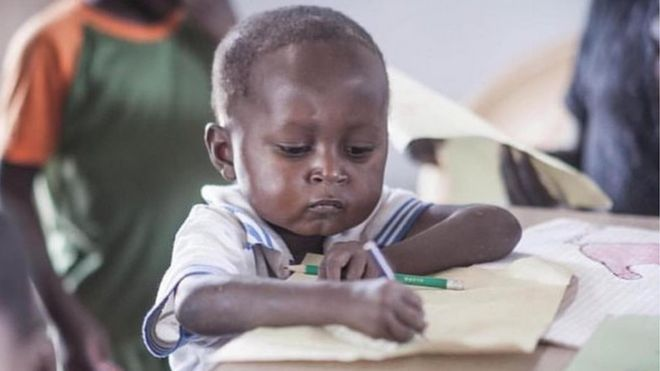 Jake, four, draws a picture with a serious look on his face - Su foto se hace viral y ayuda a recaudar fondos para la educación en su aldea