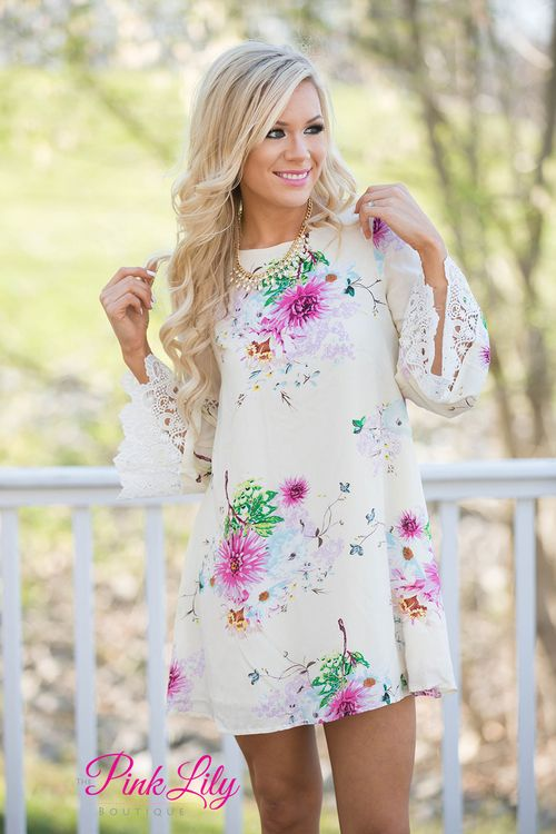 You'll be wishing your toes were in the sand, watching the sunset in this beautiful floral dress. Features a ivory bodice with vibrant floral colors, lace sleeves, and criss-cross open back.