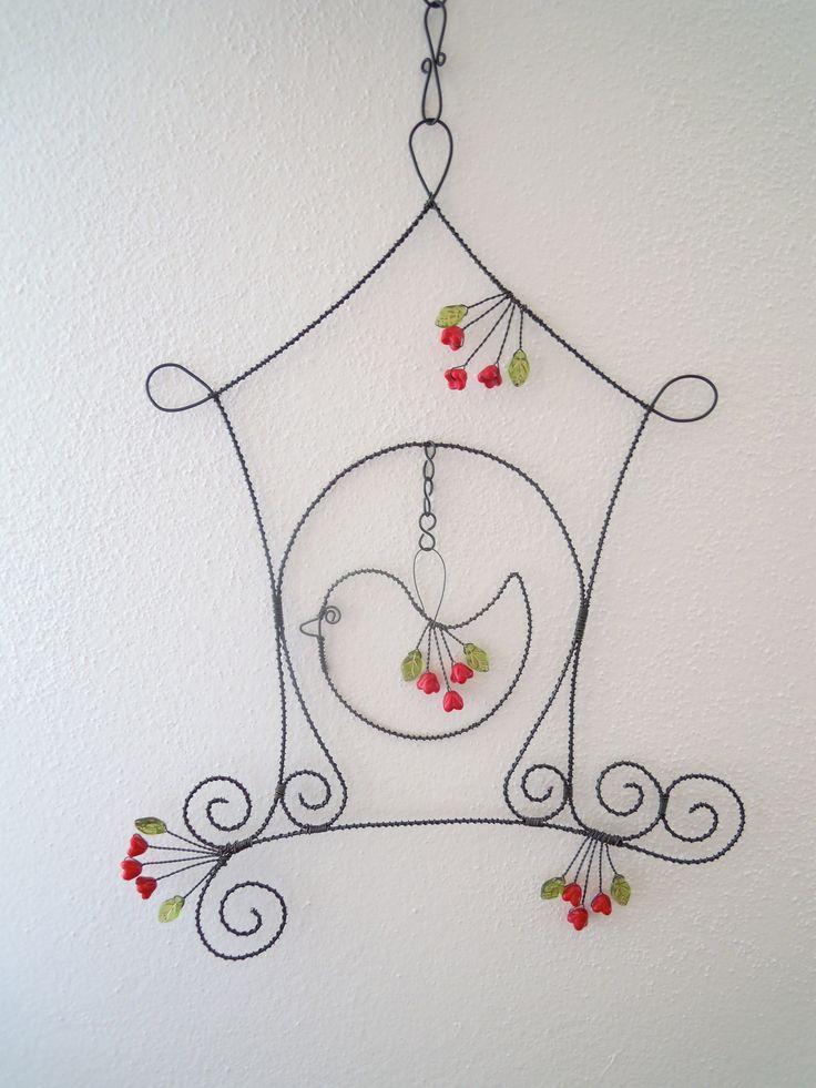 Ptačí budka v růžích- závěs Drátovaná dekorace z černého vázacího drátu, dozdobená skleněnými červenými kvítky a zelenými lístečky se zlatým žíháním. Vhodné k zavěšení na zeď, do okna, do prostoru. Velikost budky s větvičkou 23 cm x 30 cm, výška celého závěsu složeného z budky a tří háčků je cca 41 cm.