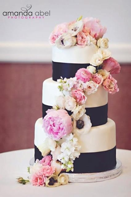 Baking a wedding cake.   Pink, black, and ivory.    Wedding cake with fresh flowers