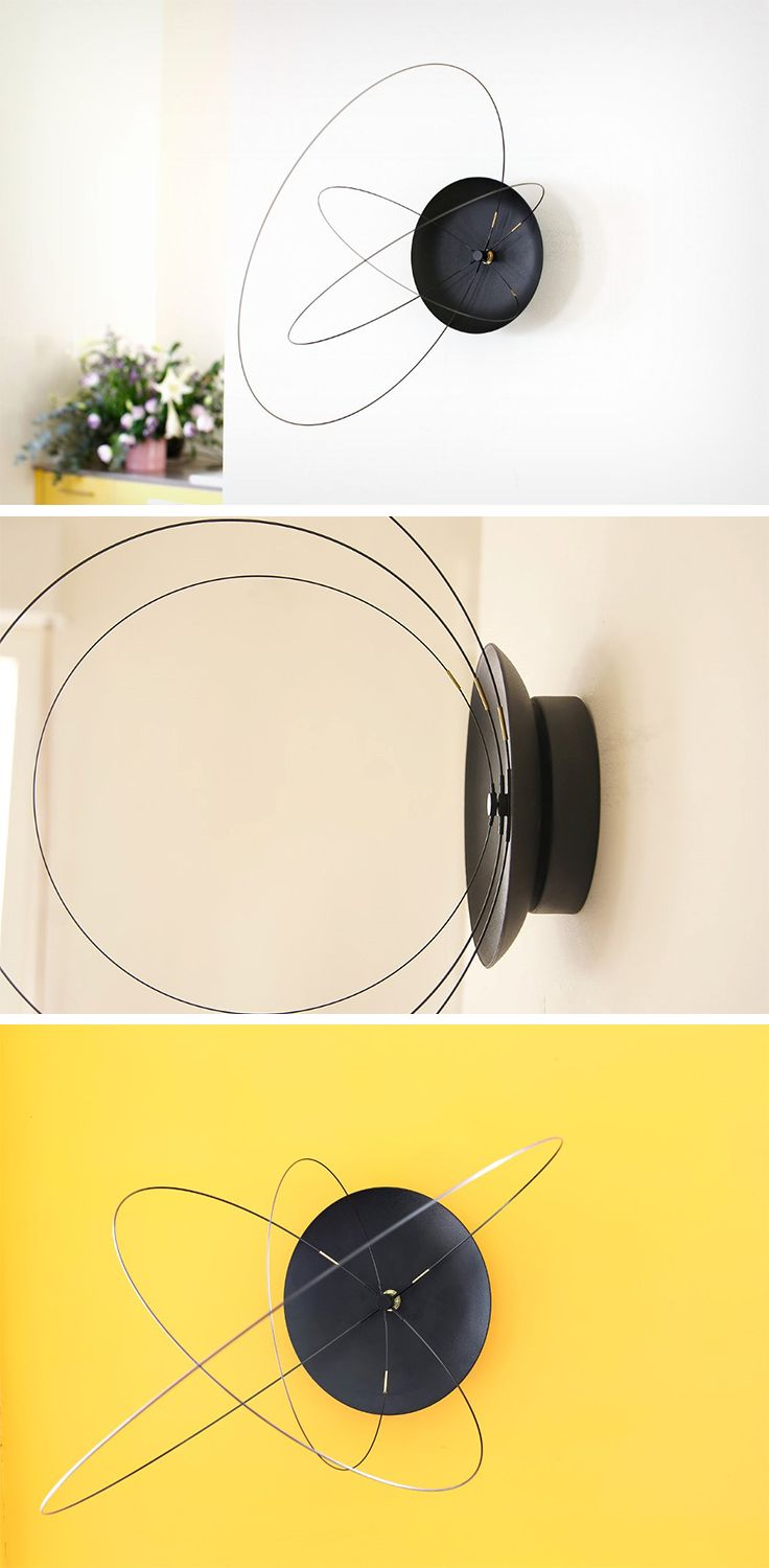 There S Something Celestial About The Orbits Clock What It Simply Does Is Trades The Conventional Hands For Hoops But Th Clock Design Wall Clock Design Clock