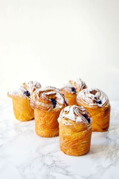 A warm blueberry cruffin for breakfast with some coffee.