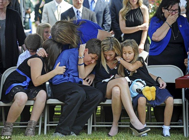 Tonja Garafola, widow of East Baton Rouge Sheriff deputy Brad Garafola, mourns with her ch...