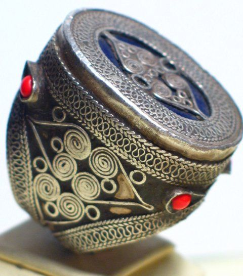Large silver Kazakh ring decorated with coral beads and topped with blue glass.
