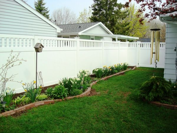 Landscaping along white privacy fence | fence makes a beautiful backdrop for this backyard landscape, along ...