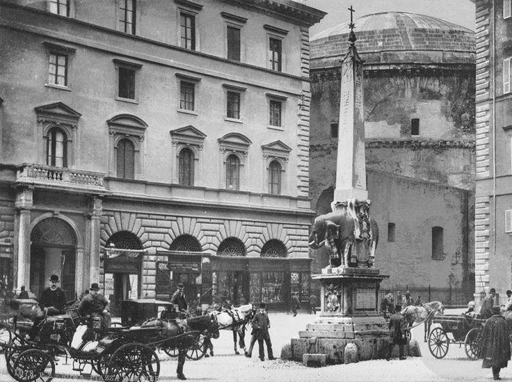 Vetturini in posa nel 1890 davanti al Palazzo dell'Accademia Ecclesiastica e sotto l'obelisco di Piazza della Minerva, sullo sfondo la possente struttura del Pantheon. L'obelisco fu alzato nel 1667 e il basamento venne commissionato al Bernini che collocò il piccolo