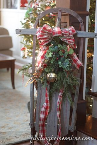 Vintage Sled Decorated... traditional – greenery, one Large bell and a plaid flannel bow w/ extra layer of ribbon hanging from bow... wire together some greenery and some interesting details – wire them to the sled (I use floral wire) – add a bow and you are done