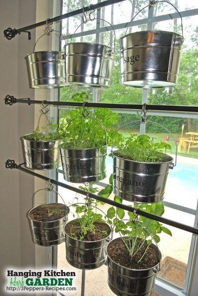 Horta vertical para janela da cozinha com vasos de ervas pendurados.