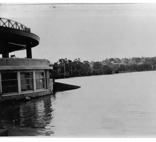 MP 9. Floods, Kooyong Club house. Looking south west from near the stadium. Gardiners Creek is in flood with the Glen Waverley railway line and Toorak houses on the hill in the background; December 1934.