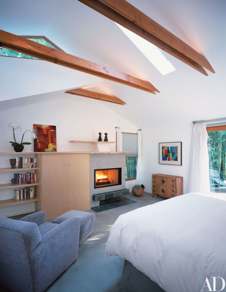This loft-style bedroom in Los Angeles features a clerestory window as well as a skylight, both of which echo the dynamic geometry formed by the roofline, angular ceiling, and wooden beams. The home, renovated by Griffin Enright Architects and architect Elyse Grinstein, boasts similar roofline windows throughout, which offer breathtaking views of the surrounding canyon.