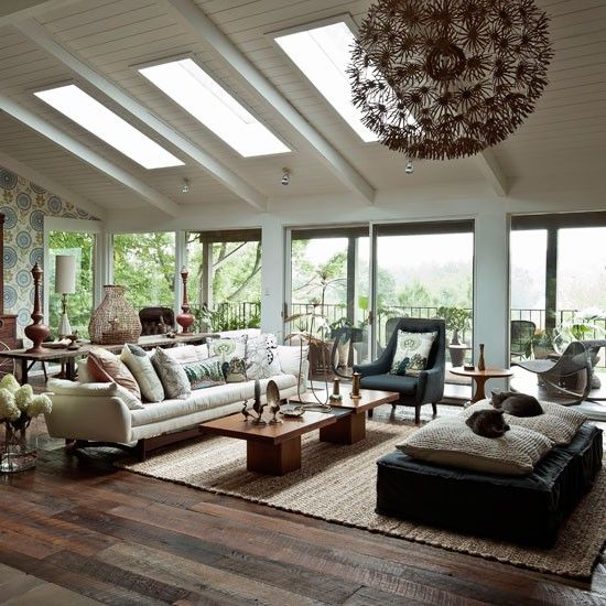 Modern wood living room. This nature-inspired living room changes with the seasons. In summer, the doors to the deck open up and the view comes inside. In winter, the soft furnishings and fireplace create a cosy feel.