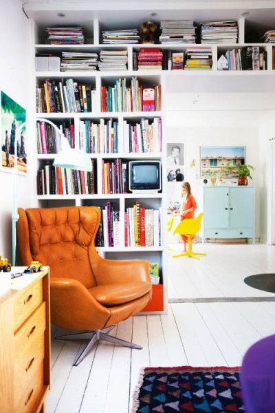 A little corner in a living room with comfy chair and floor to ceiling shelf create a pretty but small home library