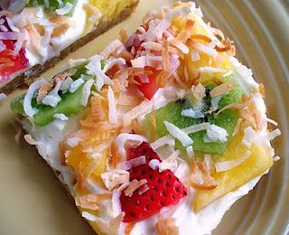 Tropical Island Fruit Pizza - For the pizza dough:  -1 roll (16.5 oz.) refrigerated sugar cookie dough  For the toppings:  -1 package (8 oz.) cream cheese, softened  -1/2 cup powdered sugar  -1 teaspoon coconut extract  -2 kiwis, sliced  -1/2 cup strawberries, sliced  -1/2 cup pineapple, sliced  -1/2 cup toasted coconut      Directions:  1. Preheat oven to 350 degrees F. Line a 13x9-inch baking pan with aluminum foil and spray with non-stick cooking spray. Press cookie dough evenly into the…