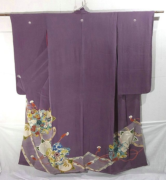 This is an elegant vintage irotomesode.  Its dyed pattern has half-laid 'misu'(bamboo curtains) and plant motifs.  Various flowers such as camellias and daffodils make up the 'neji-ume' (twisted plum blossom) motifs.    Textile is silk and has soft touch.  Lapel is hiro-eri (wide lapel).  Sleeves are gracefully long, which is the feature of kimonos from pre WWII.  There 's 5 kamon (family crests) remained undyed.