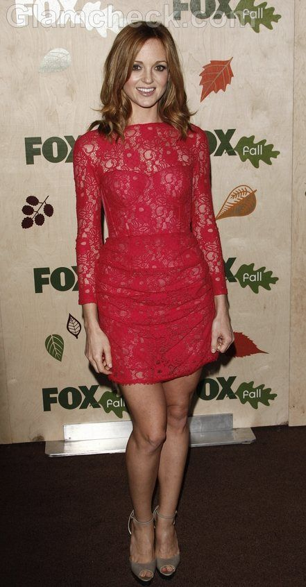 Jayma Mays in a full-sleeved, deep pink lace dress with a bateau neckline featuring a light pink strapless corseted bustier underneath