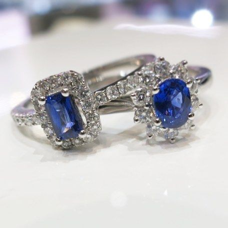 18ct white gold ring with oval sapphire surrounded by flower like shaped diamonds.  18ct white gold ring with emerald sapphire surrounded with shoulder diamonds