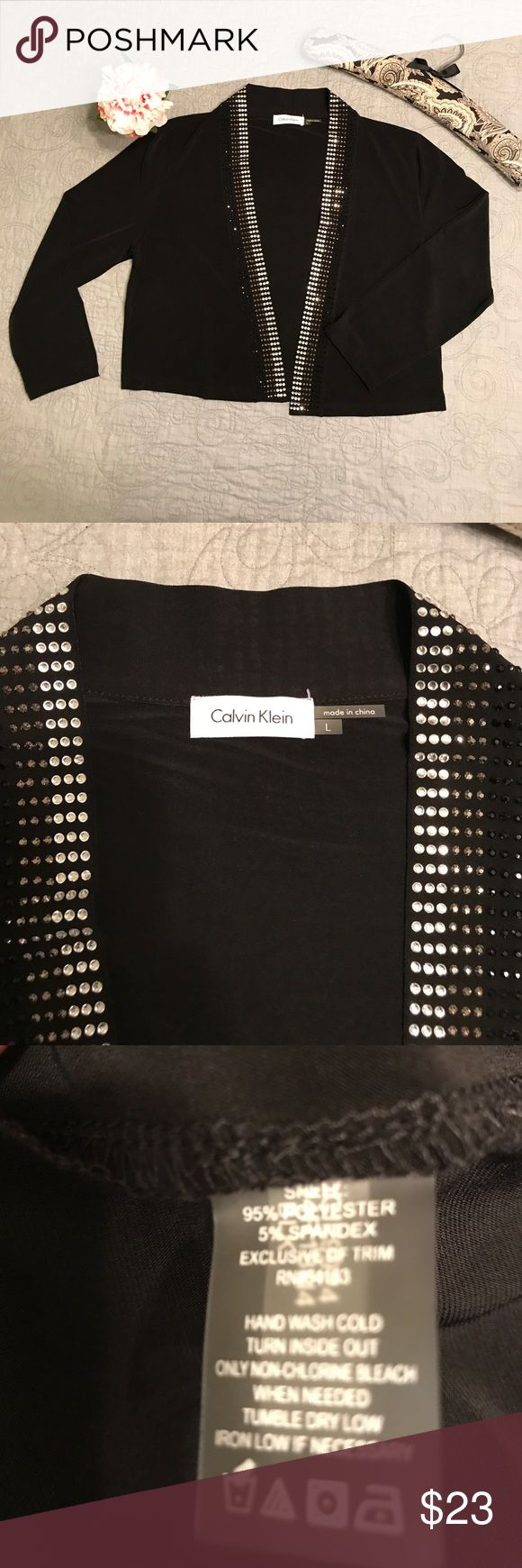 🌺 Calvin Klein Black Beaded Collar Shrug NWOT 🌺 This shrug has never been worn. It is in perfect condition. It is 95% polyester and 5% spandex. It is very elegant, yet it could easily be worn with jeans and a fun top underneath. The beaded Collar would really sparkle on the dance floor. All reasonable offers considered. 🌺 Calvin Klein Sweaters Shrugs & Ponchos