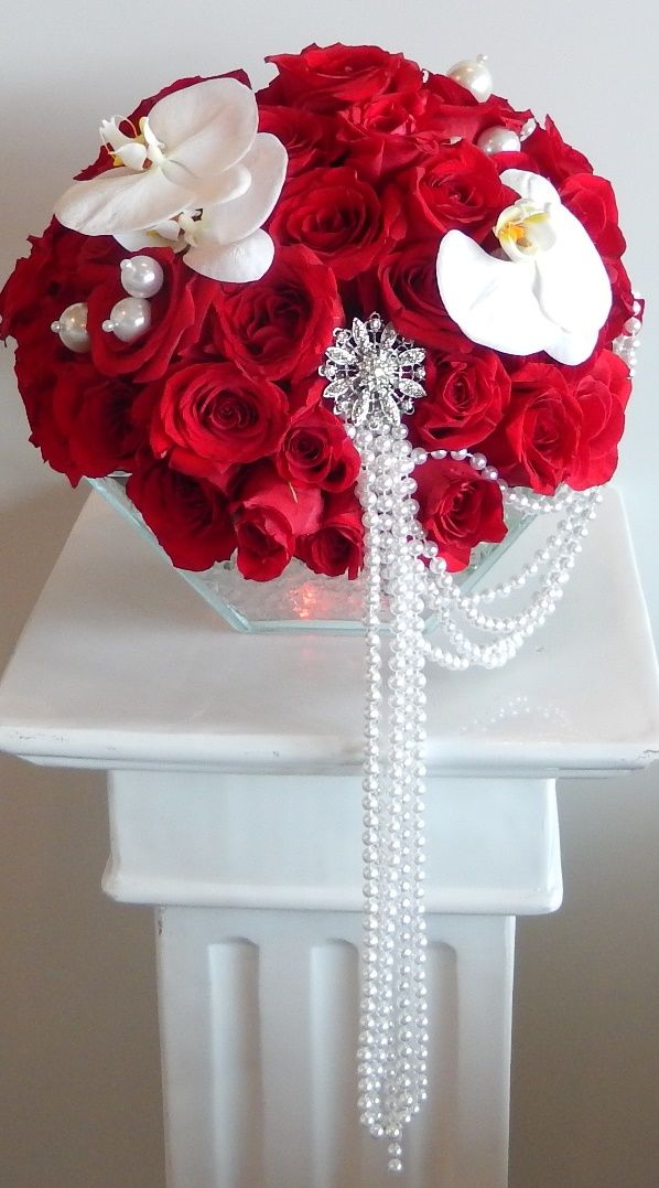 "Continuing the red theme from Dizennio Floral Boutique -Vaughan is another centre piece for a bride , this time with ""Red Paris"" roses a couple of white Phalaenopsis and pearl strands held with a large silver brooch. The vase is lit with a red light cube to give an amazing effect in a dimly lit banquet hall !"