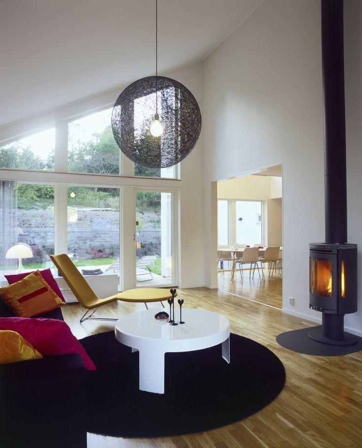 Stilrent vardagsrum med glas ända upp i tak. Perfekt att värma upp en sådan stor yta med en braskamin. @trivselhus #contura #kamin #trivselhus #bostad