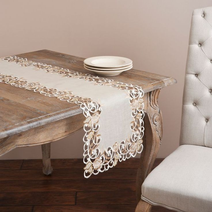 The embroidered and cutwork design on these elegant table linens are accented by the neutral color palette. Choose from a table runner or a topper to add transitional styling to your dining experience.