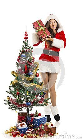 Beautiful cheerful young woman dressed in sexy Santa outfit posing with wrapped gift near decorated Christmas tree and presents, isolated on white.