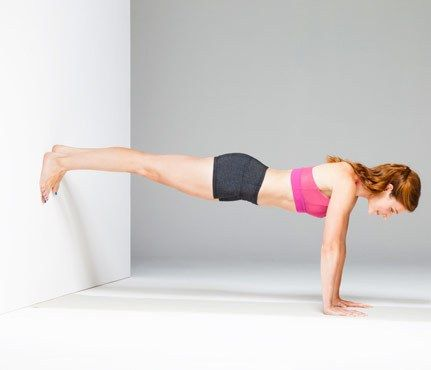 Works: shoulders, abs, obliques, lower back Start in plank, hands under shoulders, feet in line with hips and pressing into wall (as shown). Hold for 1 minute. Make it easier: Lower legs, place toes on floor with feet pressed against wall. Log this workout.