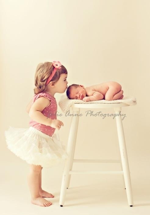 sibling kisses newborn photo