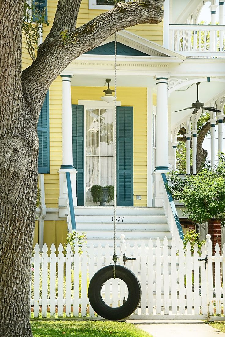 quintessential yellow country house with a white picket fence and accents. lets not forget the tree swing!