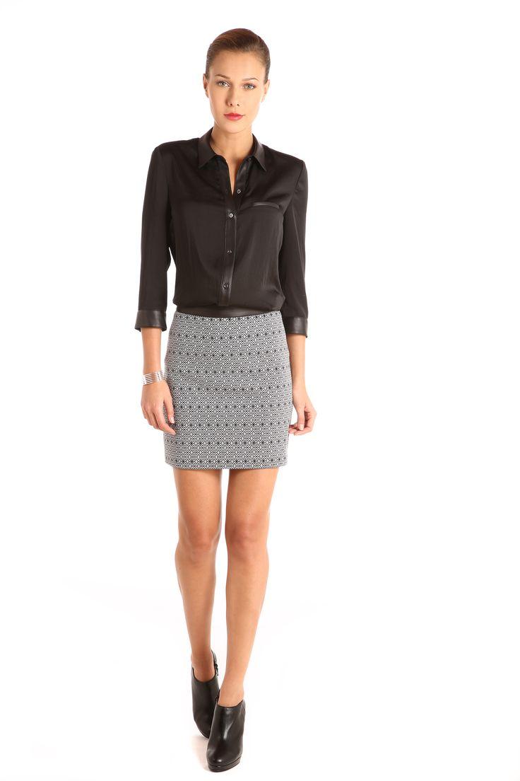 Blusa con aletilla, cuello camisero, puños y bolsa de ojal simulada en polipiel: $799. Falda corta línea A de jacquard geométrico bicolor: $799.