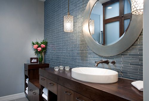 Don't overlook the color of the wood cabinetry in your bathroom. The deep, rich walnut color of this vanity grounds the space and contrasts nicely with the soft gray and blue colors of the vanity mirror and the tile backsplash wall. This is another elegant bathroom that's perfect for a long, relaxing bath.
