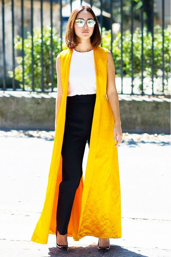 Nicole Warne of Gary Pepper Girl wears a white top, high-waisted black trousers, a silk yellow duster vest, mirrored sunglasses, and black pumps