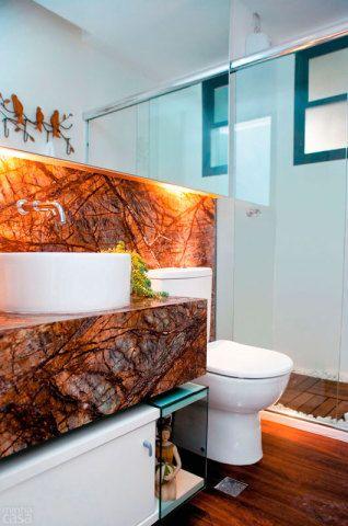 A primeira definição da arquiteta Lilia Duarte foi o mármore de tom escuro: a pedra reveste a parede e também a bancada do banheiro. Na área do boxe, seixos envolvem o deque de madeira protegido por verniz fosco. Uma lâmpada azul de led para banho dá conta da cromoterapia.