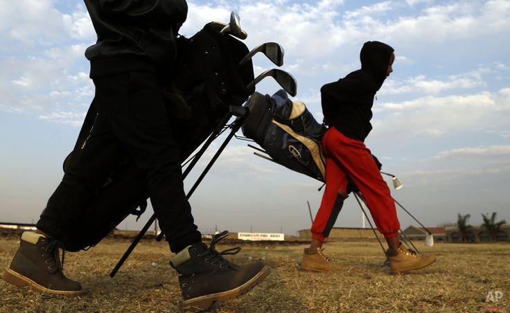 Eleven-year-old old Kgosi Motsabi, right, and his friend carry golf bags across the park in Katlehong township, east of Johannesburg, South Africa, Thursday, July 16, 2015. (AP Photo/Themba Hadebe)