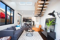 Living & dining areas open to deck & garden, wall art, floor lamp, timber stairs, skylights